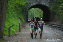 Megan DiGregorio of Baltimore running top master Pete LoBianco #204 just south of the Howard Tunnel, in the pouring rain.