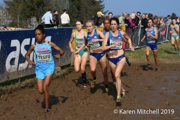 Stephanie Bruce of USA, a veteran of two World XC heads through the mud, just ahead of three USA teammates. Dolshi Tesfu of Eritrea, placed 38th, and Emily Brichacek of Australia, placed 35th.