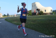 Lacy Deller in July 4 patriotic gear gives me the peace sign while rounding the Shoe House.