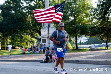 Miguel Encinas of Bridgeport, Ohio runs the Debbie Green Memorial 5K with the USA flag.